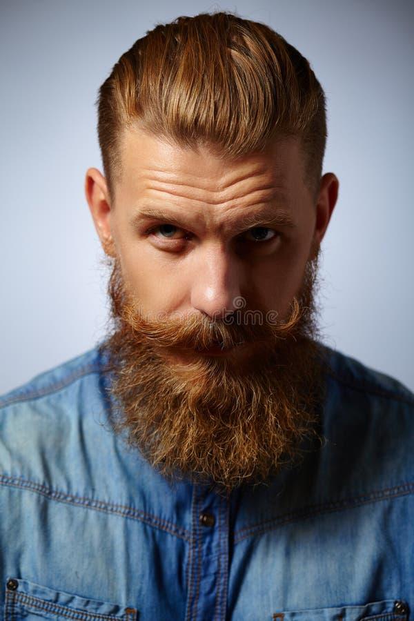 Stående av den brutala mannen med skägget och mustaschen royaltyfria bilder