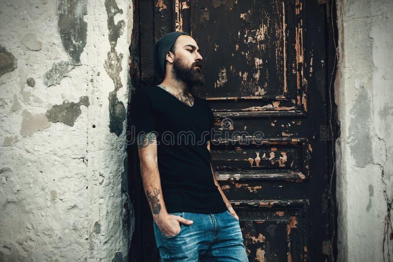 Stående av den brutala skäggiga mannen som bär den tomma t-skjortan arkivfoto