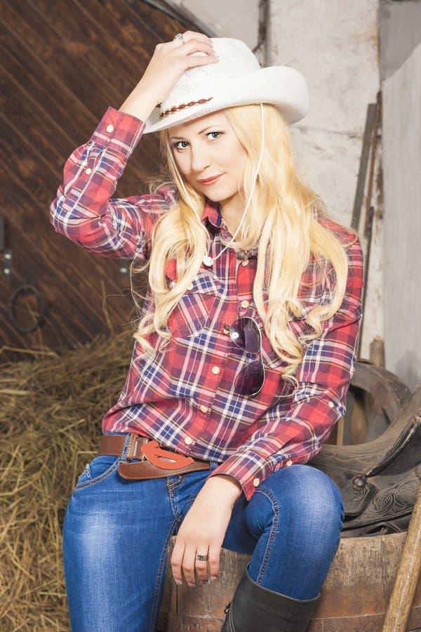 Stående av den Caucasian blonda cowgirlen inom av lantgårdhuset royaltyfri bild