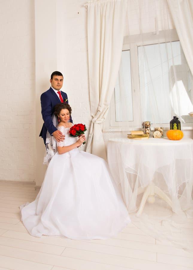 Stående av den Caucasian bruden och den asiatiska brudgummen inomhus arkivfoton