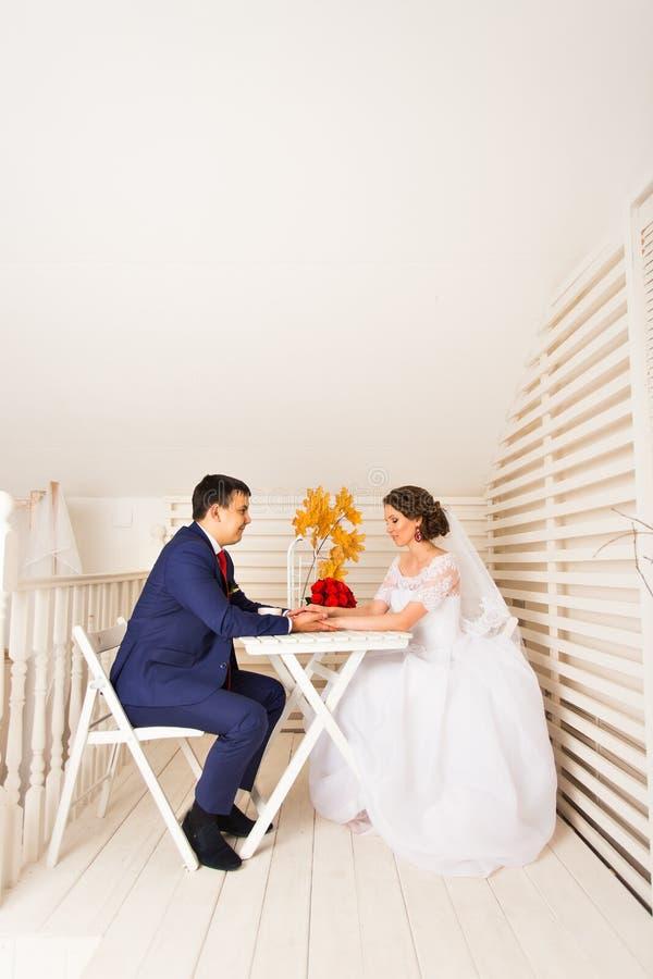 Stående av den Caucasian bruden och den asiatiska brudgummen inomhus arkivfoto