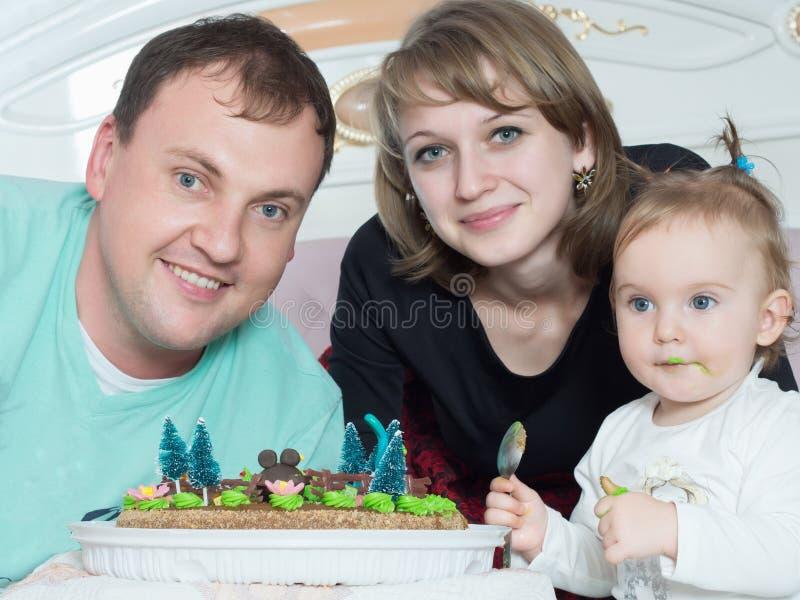 Stående av den caucasian familjen på lycklig födelsedag med kakan royaltyfri bild
