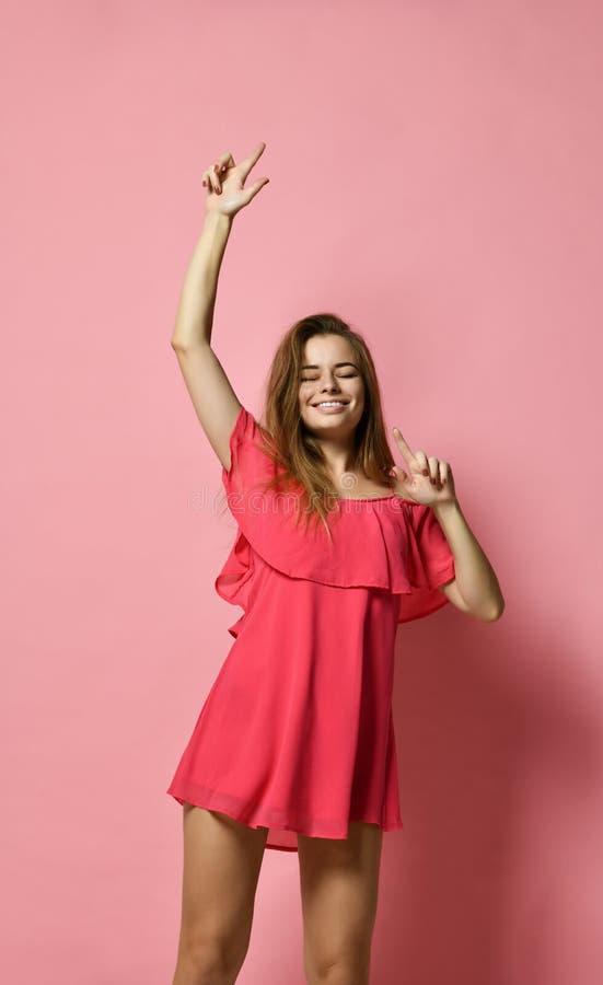 Stående av den Caucasian flickadansen för brunett mot den rosa väggen med leende som jublar bra lynne royaltyfria foton