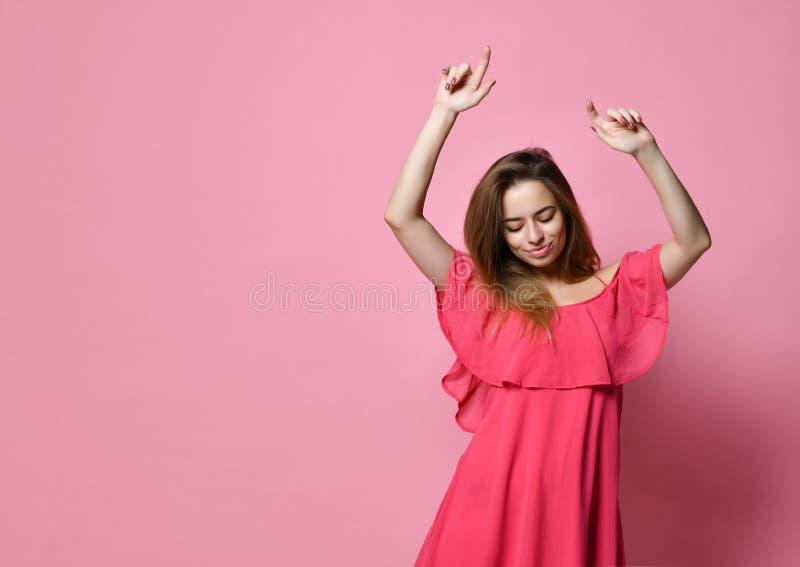 Stående av den Caucasian flickadansen för brunett mot den rosa väggen med leende som jublar bra lynne arkivfoto