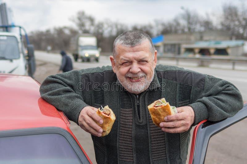 Stående av den Caucasian höga chauffören som äter lyulyakebab royaltyfria foton