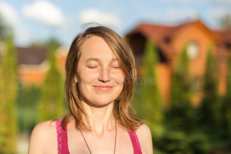 Stående av den caucasian kvinnan för ung brunett som utomhus ler med stängda ögon Guld- timmesolljus på solnedgången Gree arkivfoto