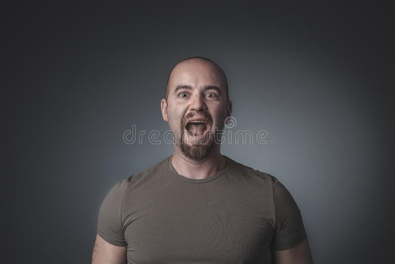 Stående av den caucasian mannen som skriker och ser rakt främst av kameran royaltyfri bild