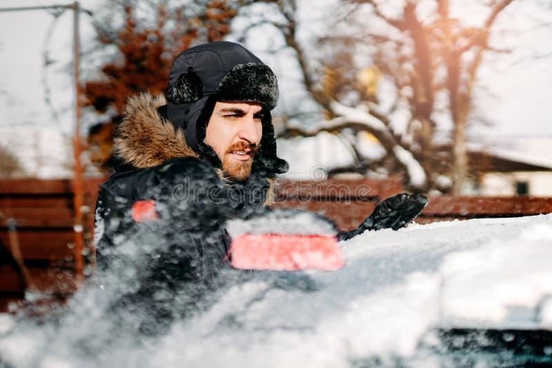 Stående av den caucasian mannen som tar bort snö från bilen Vintertransportbegrepp royaltyfri foto