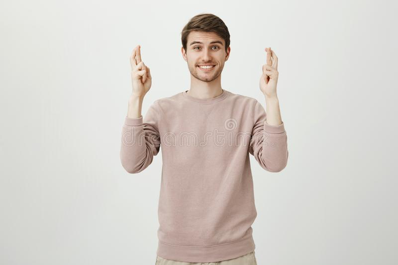 Stående av den charmiga caucasian mannen med borstet som lyfter händer med korsade fingrar och ler som uttrycker villighet fotografering för bildbyråer