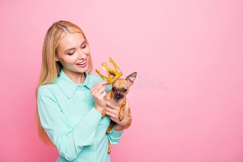 Stående av den charmiga damen som rymmer hennes älskvärda husdjur som sätter tiaran på huvudet som bär denfärgade skjortan som is arkivfoto