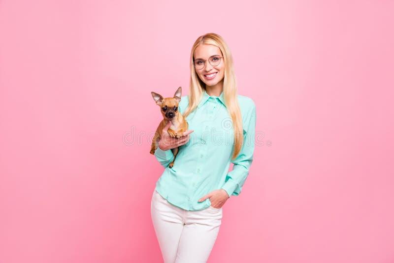 Stående av den charmiga flickan som rymmer hennes för krickaskjorta för husdjur bärande glasögon för eyewear för byxa för flåsand arkivbilder