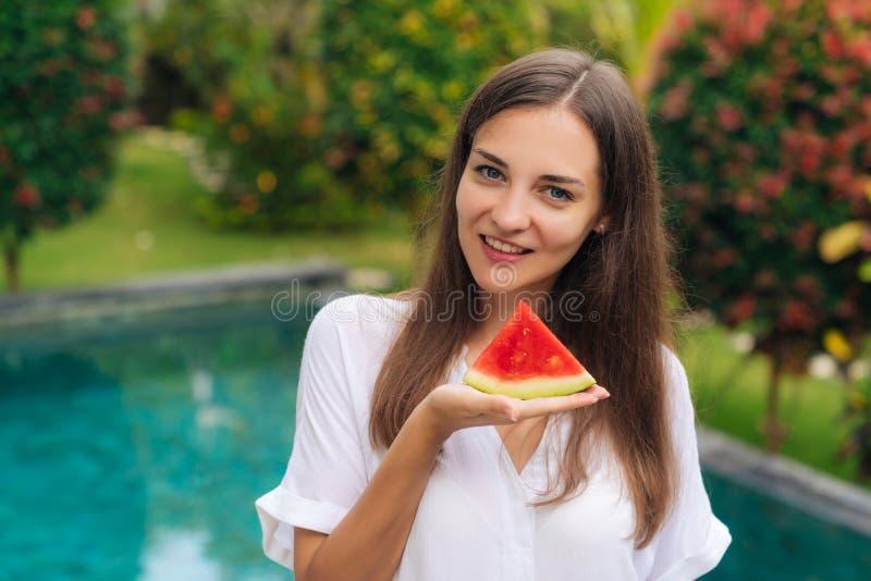 Stående av den charmiga le flickainnehavskivan av den saftiga vattenmelon i hennes hand arkivbild