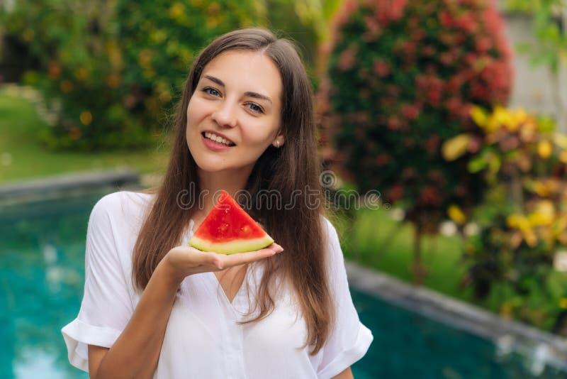 Stående av den charmiga le flickainnehavskivan av den saftiga vattenmelon i hennes hand fotografering för bildbyråer