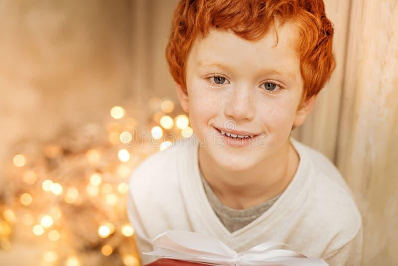 Stående av den charmiga ungen som ler, medan rymma gåvan royaltyfria bilder
