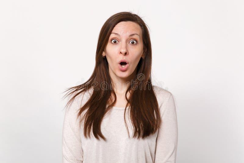 Stående av den chockade häpna nätta unga kvinnan i ljus kläder som ser kameran som håller öppet för mun isolerat på vit arkivbild