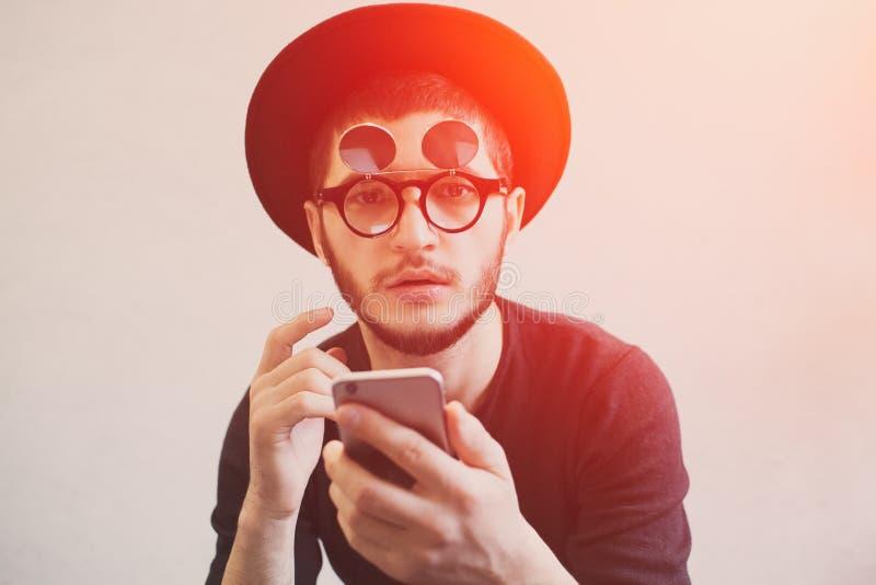 Stående av den chockade mannen med smartphonen i händer, bärande hipstersolglasögon och svart hatt, över vit bakgrund, med arkivbild