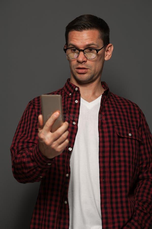 Stående av den chockade mannen som talar på telefonen royaltyfri foto