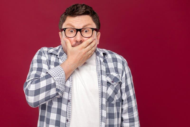Stående av den chockade mellersta åldriga affärsmannen i tillfälligt rutigt skjorta- och glasögonanseende som täcker hans mun och fotografering för bildbyråer