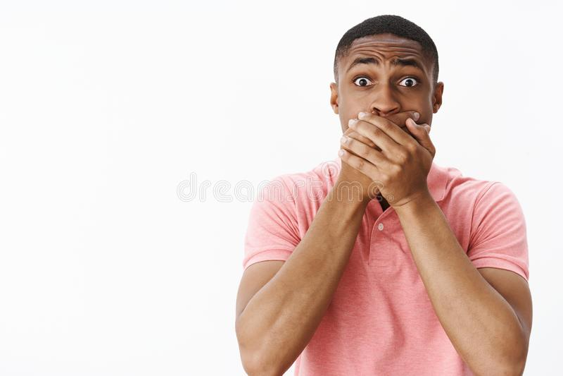 Stående av den chockade unga mannen för bekymrad och bekymrad otrygg afrikansk amerikan som rymmer händer på kippa känsla för mun royaltyfri bild