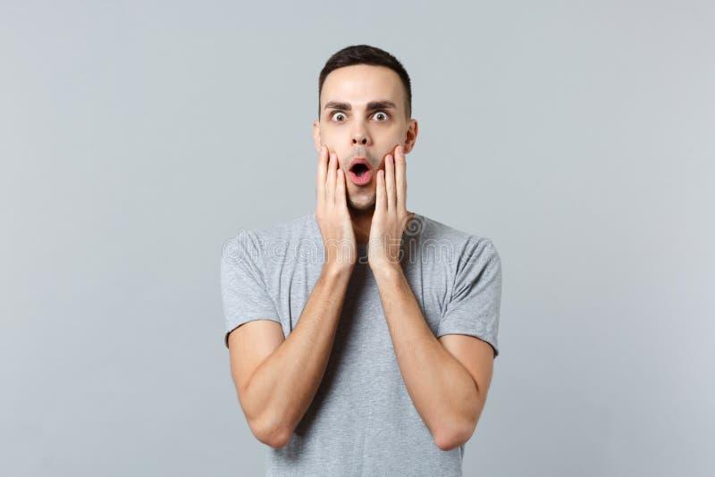 Stående av den chockade upphetsade unga mannen i tillfällig kläder som håller munnen öppen som sätter händer på framsidan som iso arkivbilder