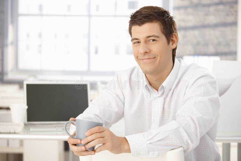 Stående av den content affärsmannen med koppen arkivfoto