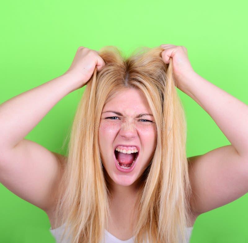 Stående av den desperata blonda unga kvinnan som drar hår mot gre royaltyfria bilder