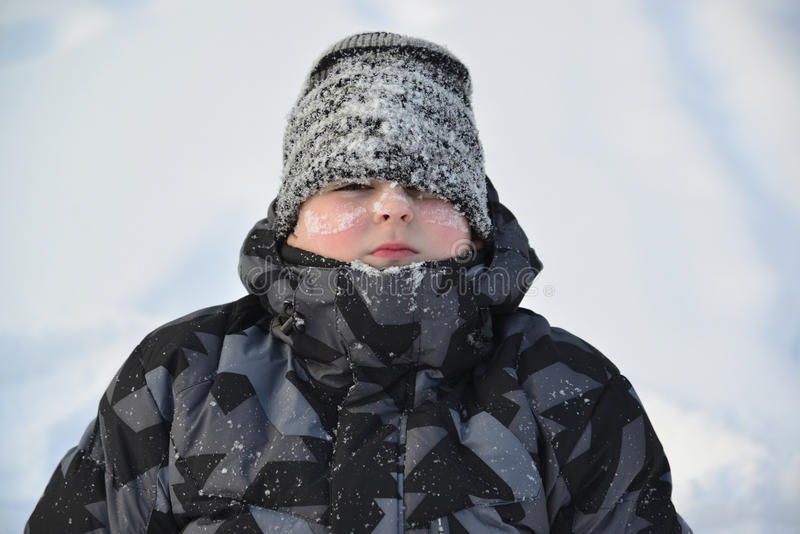 Stående av den djupfrysta pojken i vinter arkivbild