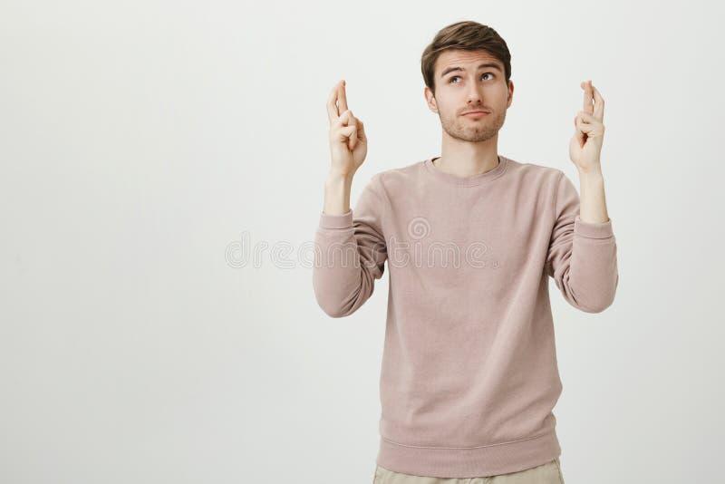 Stående av den drömlika attraktiva caucasian mannen som åt sidan ser med fundersamt uttryck, medan lyfta händer med korsat royaltyfri fotografi