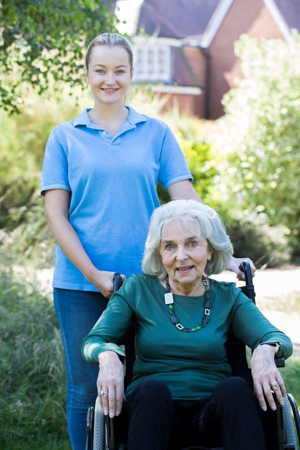 Stående av den driftiga höga kvinnan för vårdare i rullstol utanför Hom arkivfoto
