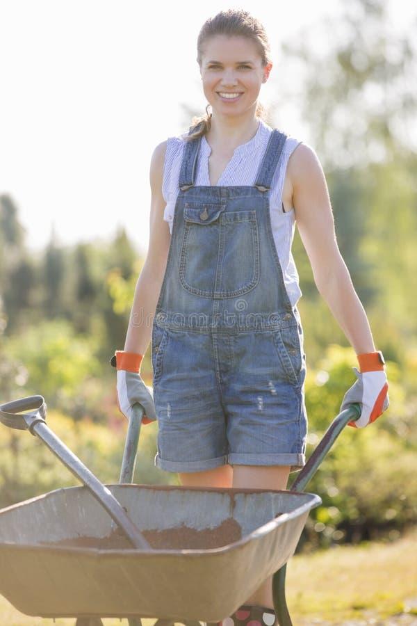 Stående av den driftiga skottkärran för lycklig kvinnlig trädgårdsmästare på trädgården royaltyfri fotografi