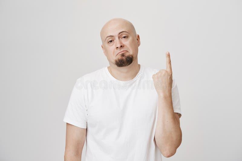 Stående av den dystra och unsatisfied skalliga europeiska mannen med skäggvisningpekfinger eller nummer ett som uttrycker royaltyfri fotografi