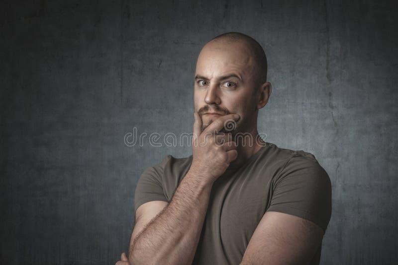 Stående av den eftertänksamma caucasian mannen med t-skjortan och mörk bakgrund royaltyfri fotografi