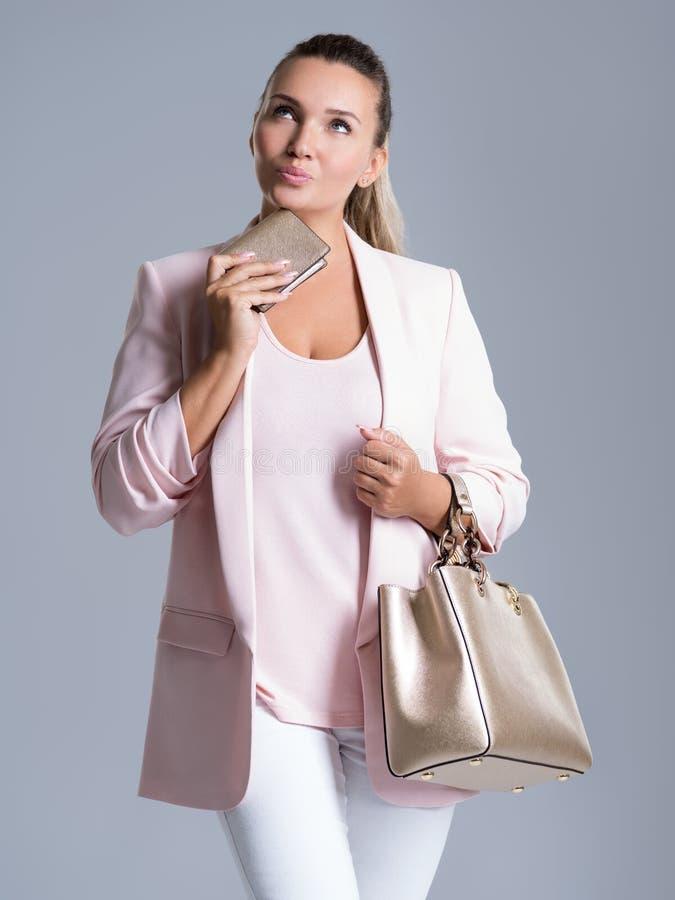 Stående av den eftertänksamma kvinnan med handväskan i hand och en handväska i mummel arkivfoton