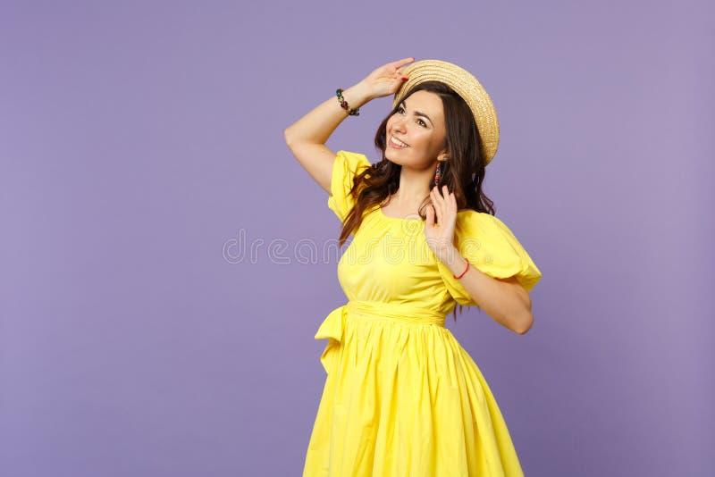 Stående av den eftertänksamma le unga kvinnan i den gula klänningen som håller handen på sommarhatten som ser upp på pastellfärga fotografering för bildbyråer