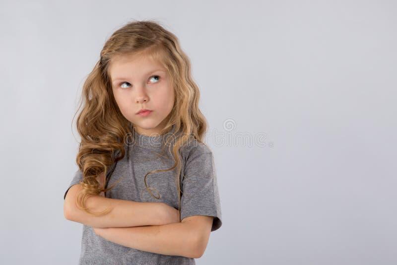 Stående av den eftertänksamma lilla flickan som isoleras på en vit bakgrund arkivbilder