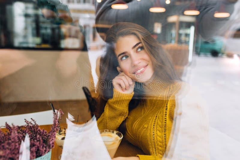 Stående av den eftertänksamma romantiska flickan bak fönster som sitter på tabellen med koppen kaffe och blommor på den n?tt arkivbild