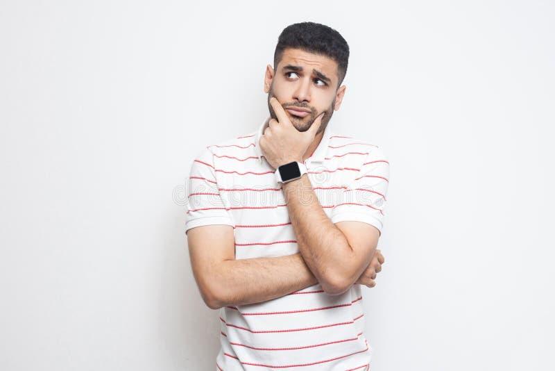 Stående av den eftertänksamma stiliga skäggiga unga mannen i randigt t-skjorta anseende och att trycka på hans framsida och att s arkivfoto