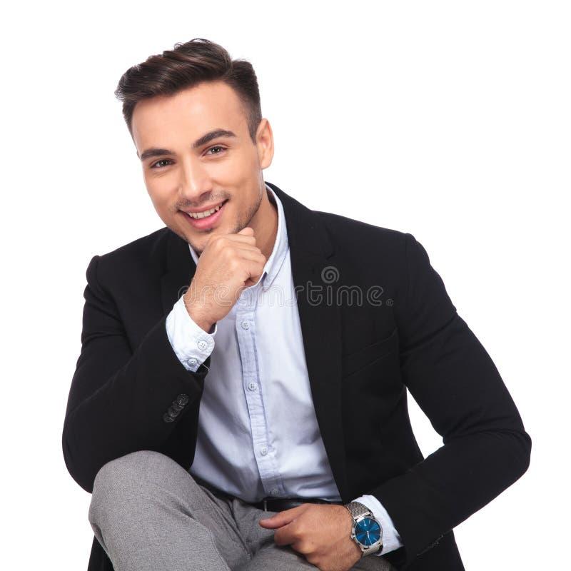 Stående av den eftertänksamma unga affärsmannen som ler och sitter royaltyfria foton