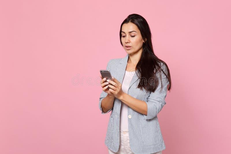 Stående av den eftertänksamma unga kvinnan i randigt omslag genom att använda mobiltelefonen som skriver smsmeddelandet som isole arkivfoto