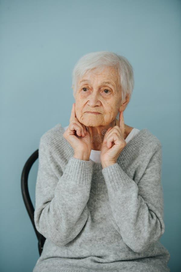 Stående av den elderely gråa haired kvinnan i en bekväm tröja hemma arkivbild