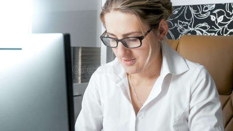 Stående av den eleganta kvinnan i den vita blusen som i regeringsställning arbetar på datoren royaltyfri fotografi