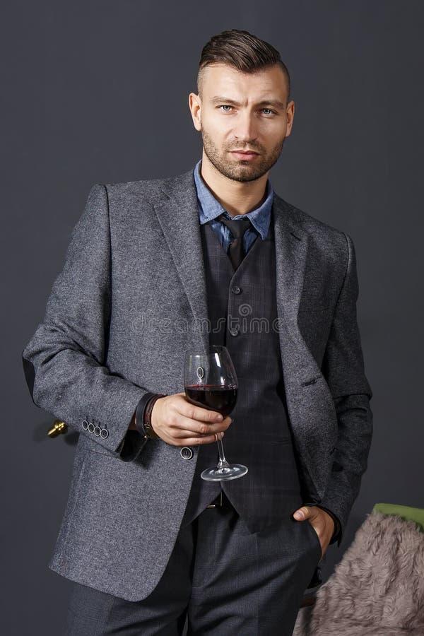 Stående av den eleganta säkra stiliga mannen i affärsdräkt med exponeringsglas av rött vin på grå väggbakgrund royaltyfria foton
