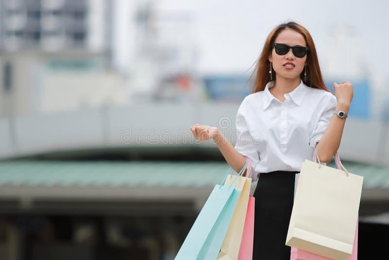 Stående av den eleganta unga asiatiska kvinnan med den färgrika shoppingpåsen Mjuk fokus, livsstil fotografering för bildbyråer