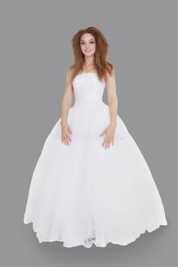 Stående av den eleganta unga brunetten i bröllopsklänningen som står över grå bakgrund arkivbilder