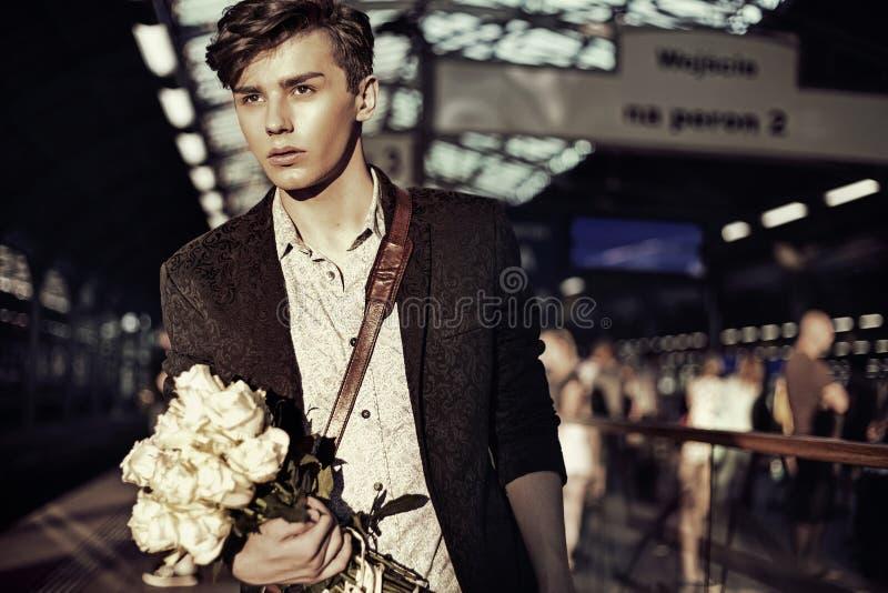 Stående av den eleganta unga grabben med blommor arkivfoto