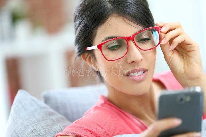 Stående av den eleganta unga kvinnan som använder smartphonen royaltyfri fotografi