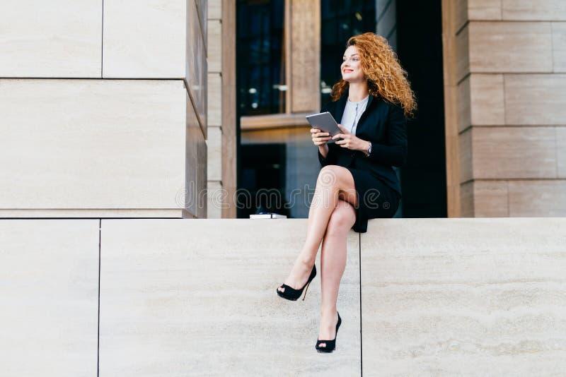 Stående av den eleganta ursnygga kvinnan i svart dräkt och hög-heeled skor som har spensliga långa ben som sitter med den moderna royaltyfri foto