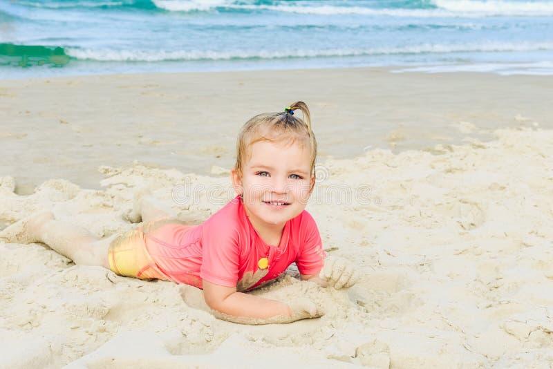 Stående av den emotionella förtjusande litet barnflickan i den skyddande baddräkten för sol som ligger på sanden på stranden och  arkivbild