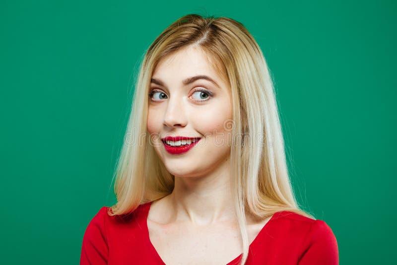 Stående av den emotionella flickan med röda sinnliga kanter och långt hår i studio på grön bakgrund arkivfoto