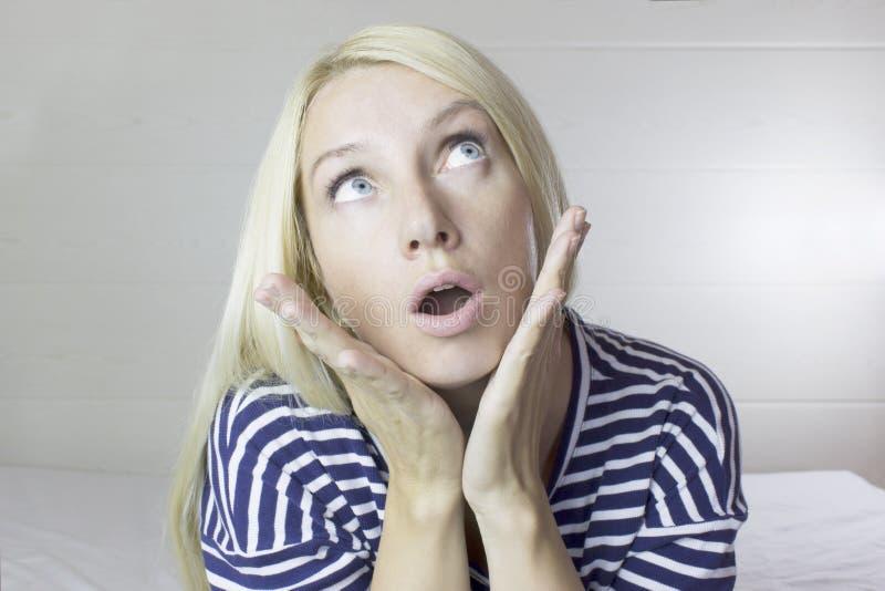 Stående av den emotionella fundersamma undrade härliga gulliga blonda kvinnan, ljus - grå bakgrund Lady för ansiktsbehandling Exp arkivfoton